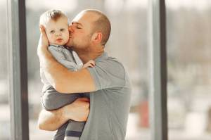 photo of guy kissing a baby